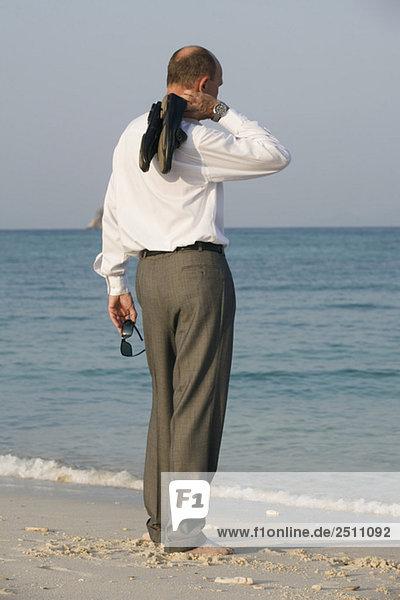 Asien  Thailand  Geschäftsmann am Strand  Rückansicht