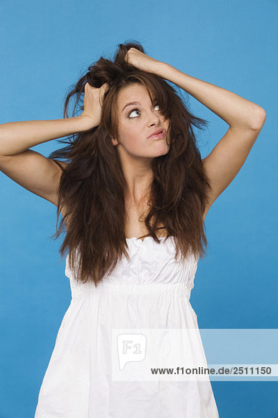 Junge Frau reißt sich die Haare  Porträt
