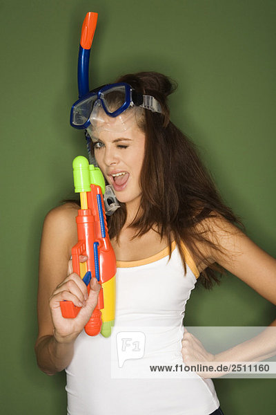 Young woman wearing diving goggles  holding a water pistol