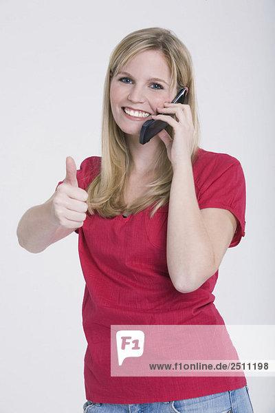 Junge Frau mit Handy  Daumen hoch  Portrait