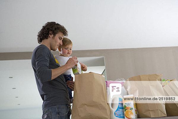 Vater und Baby mit Einkaufstaschen