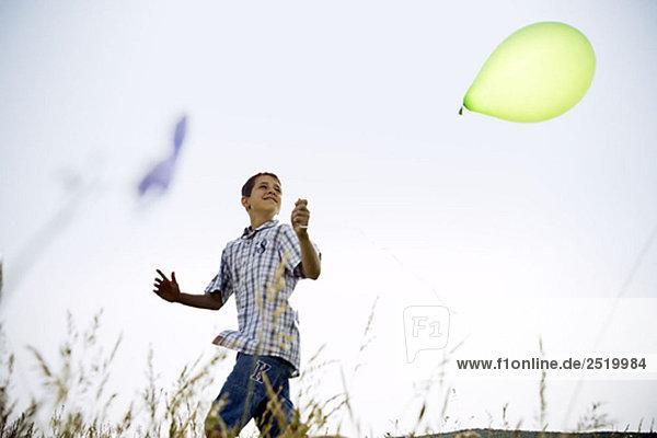 Junge läuft mit Ballon