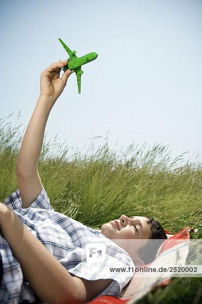 Junge im Liegen spielend mit dem Flugzeug