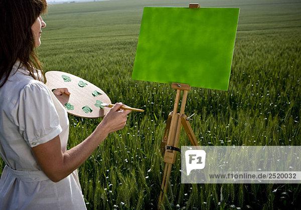 Frauenmalerei im Weizenfeld