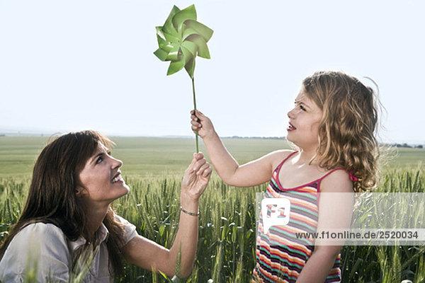 Frau und Kind halten Spielzeug Windmühle Frau und Kind halten Spielzeug Windmühle