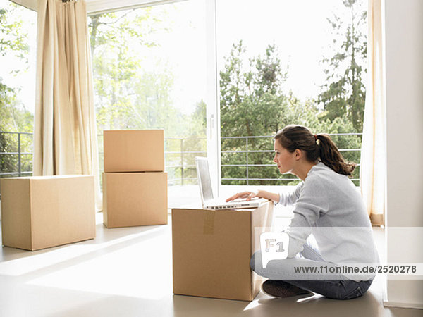 Woman on computer  moving boxes around