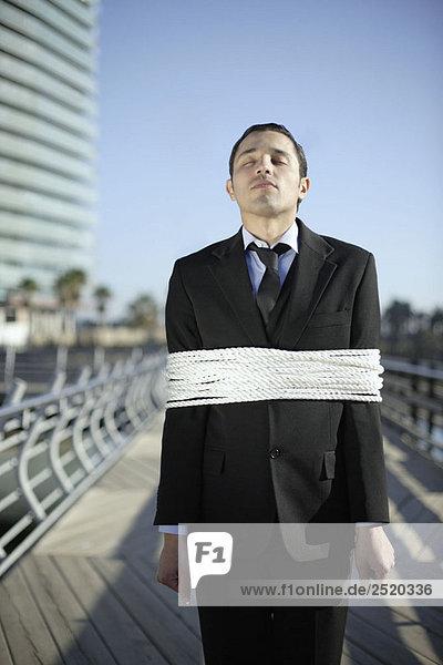 Geschäftsmann mit Seilen im Freien gefesselt