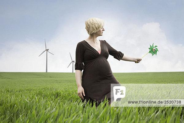 Schwangere Frau spielt mit Windmühle Schwangere Frau spielt mit Windmühle
