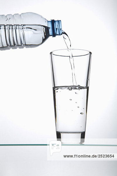 Drinking glass getting filled from a plastic bottle