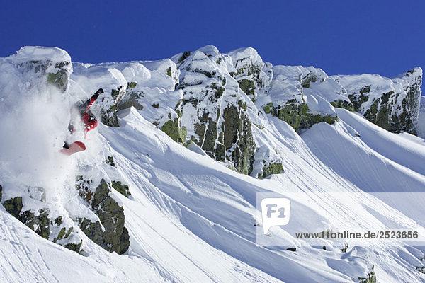 Snowboarder springt vor Bergkulisse  fully_released