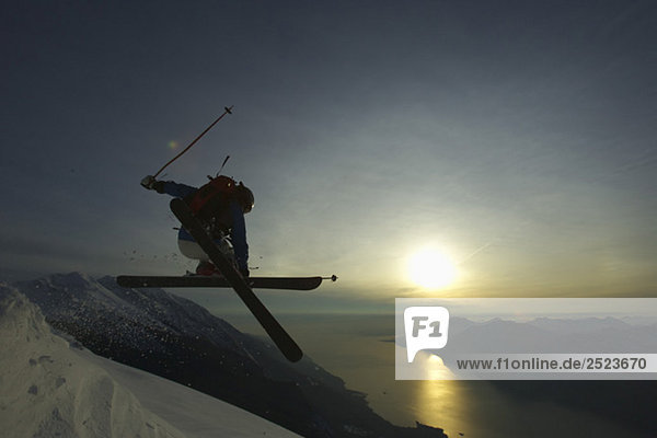 Springender Skifahrer vor untergehender Sonne  fully_released