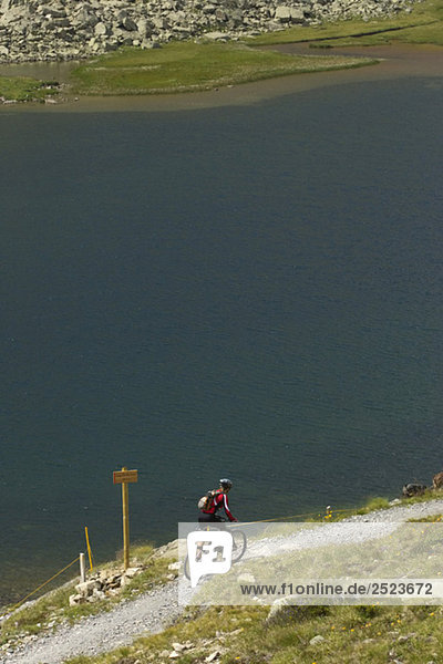 Mountainbikefahrer fährt an einem Ufer entlang  fully_released