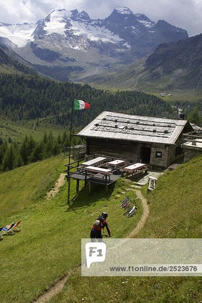 Mountainbikefahrer fährt zu einer Berghütte  fully_released