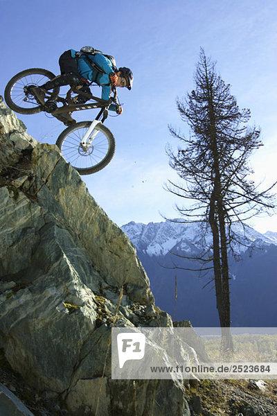 Downhillfahrer fährt einen steilen Felsen runter  fully_released
