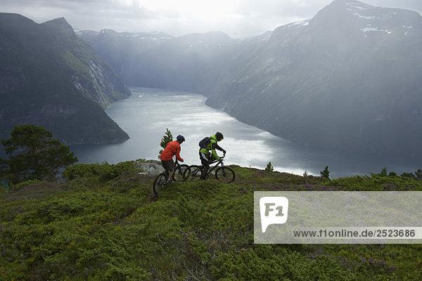 Zwei Fahrradfahrer vor einem Fjord  fully_released