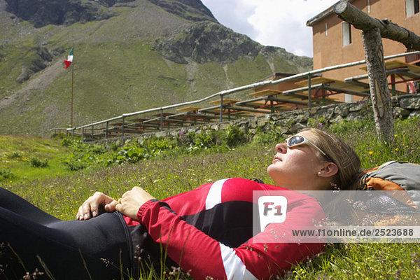 Junge Frau ruht sich auf einer Alm aus  fully_released