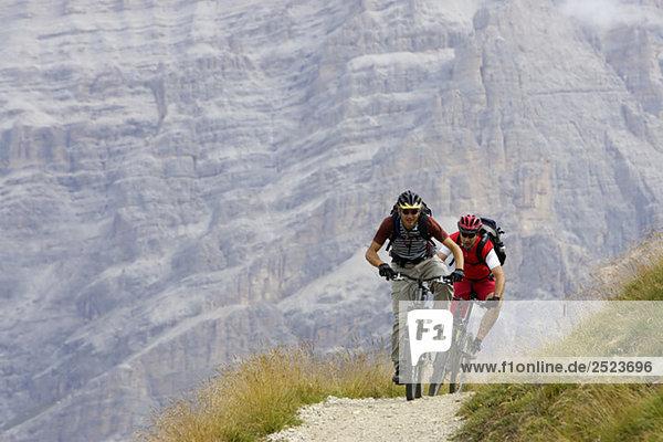 Zwei Mountainbikefahrer vor einer Felswand  fully_released