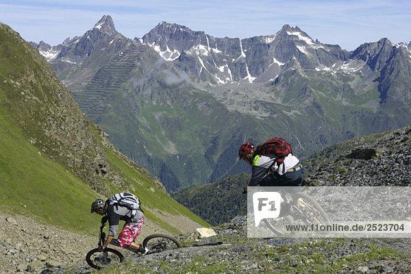 Zwei Downhillfahrer rasen einen Berg hinunter  fully_released