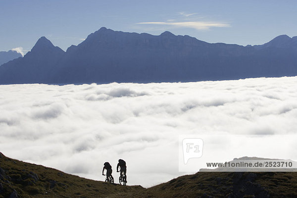 Zwei Mountainbikefahrer vor einem Wolkenmeer  fully_released