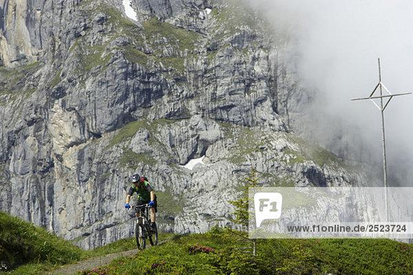 Mountainbikefahrer vor einer Felswand  fully_released