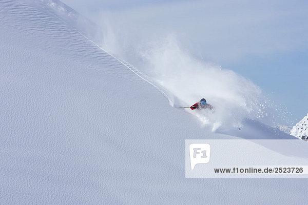 Skifahrer fährt eine enge Kurve auf unberührtem Schnee  fully_released