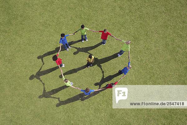 Gruppe von Kindern hält hände in einem Kreis