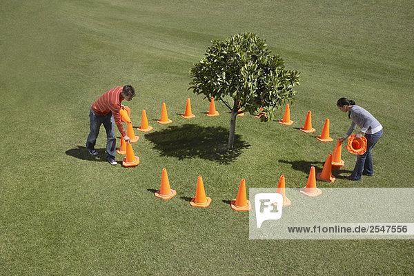 Paar platzieren Traffic Cones um Baum