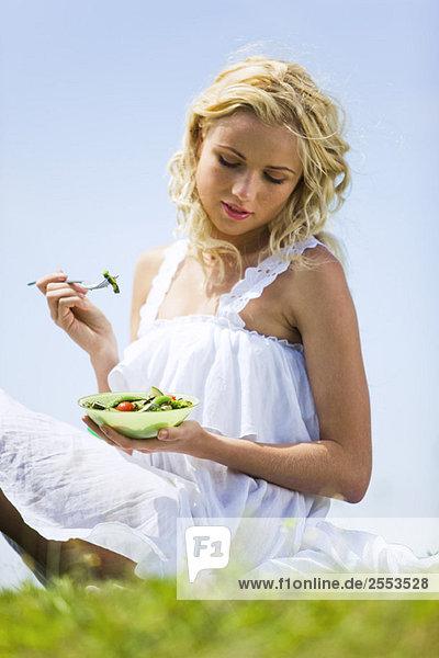 Junge Frau isst Gemüse Junge Frau isst Gemüse
