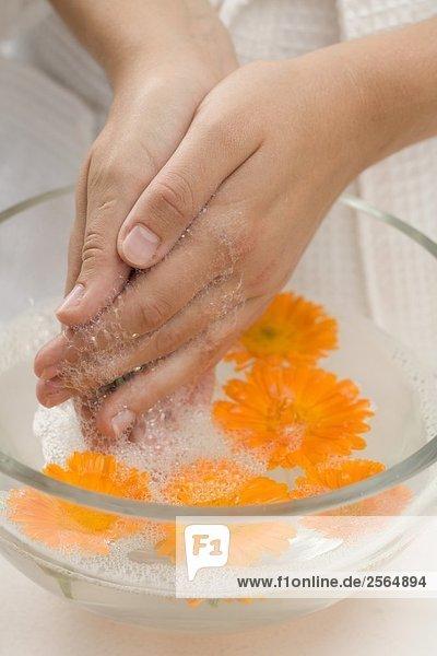 Frau wäscht ihre Hände in Seifenwasser mit Ringelblumen