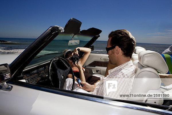 Frau machen ein Foto der Freund im Auto