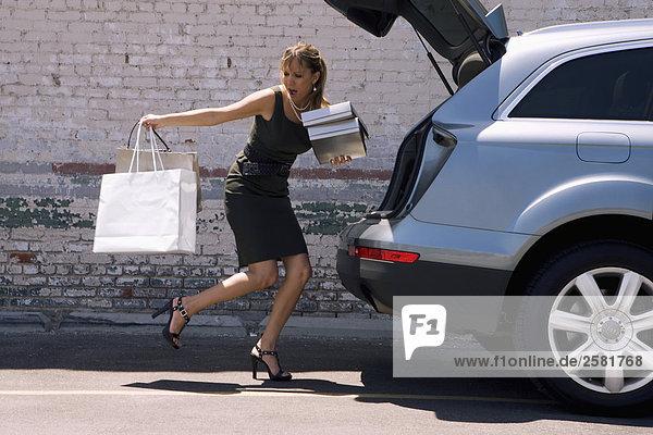 Frau zu Einkaufstaschen neben Auto löschen