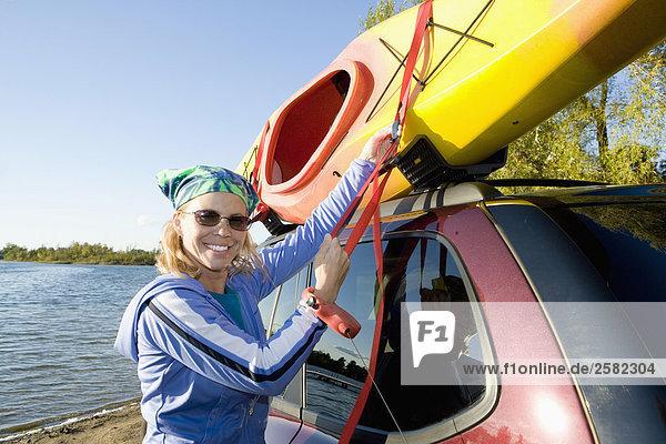 Frau lädt Kajak zu Dach ihre SUV am Seeufer