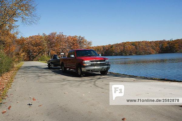 roten Lieferwagen Schleppendes Speedboat zum See