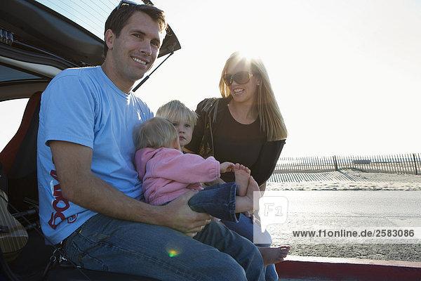 Junge Familie gesenkter Blick auf Boot von Cost am Strand