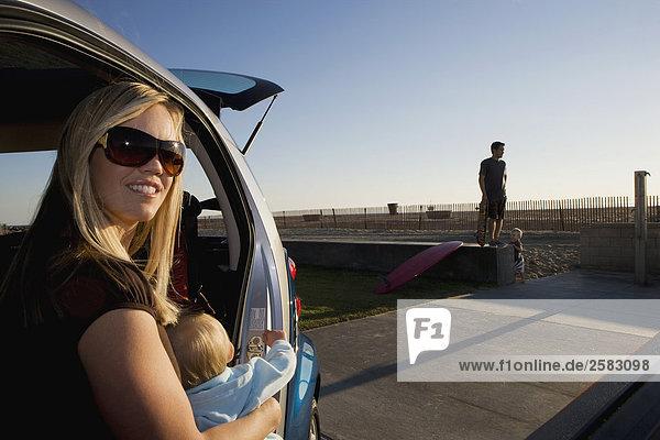 Junge Frau und Kind in Cost am Strand sitzen