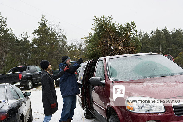 husband and wife placing Christmas tree on car roof