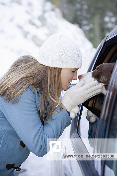 Junge Frau umarmt einen Hund durch SUV Fenster