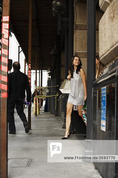 junge Frau junge Frauen tragen Tasche Gebäude kaufen aussteigen