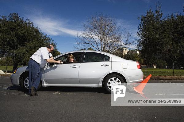 Fahrlehrer auf umgestoßen orange Kegel