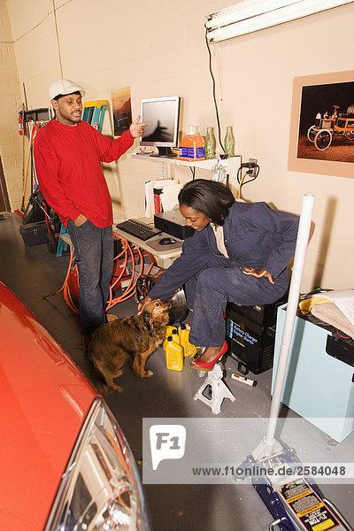 Mechaniker überprüft Computer während Frau Haustier Hund im garage