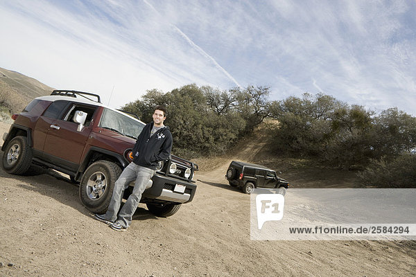 Mann beugt sich gegen seine SUV als eine weitere Anstiege hill
