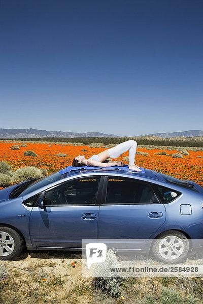 Junge Frau Übendes Yoga auf Dach des blue Toyota Prius