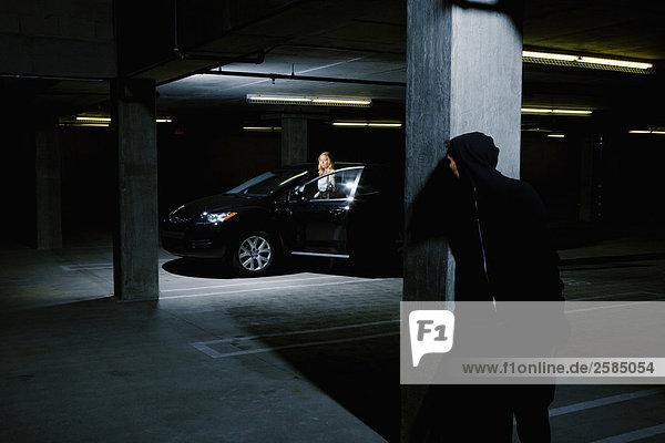 Prowler versteckt sich hinter Säule als Frau Auto im Parkplatz Eintritt