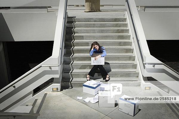 Geschäftsfrau sitzt auf Schritte von ausgelassenen Felder Papierkram