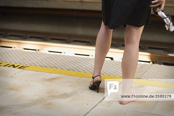 Junge Frau auf Zug-Plattform mit gebrochenen Schuh