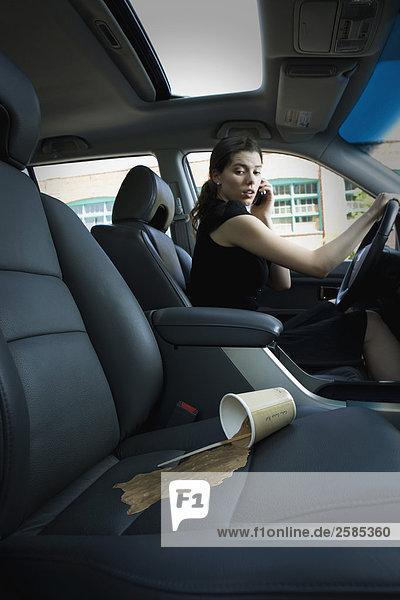 Young Frau blickt auf Kaffee Spill auf Beifahrersitz