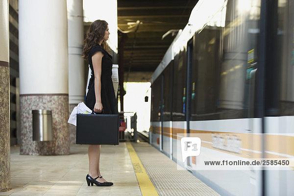 Junge Frau mit Aktenkoffer und Box auf Zug-Plattform