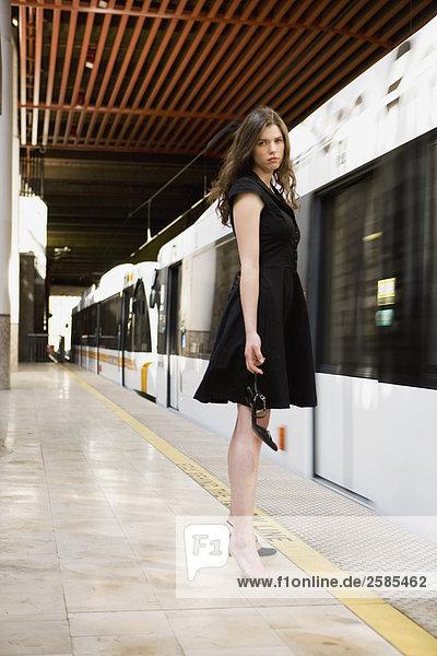 Junge Frau mit gebrochenen Schuh als Zug ankommt