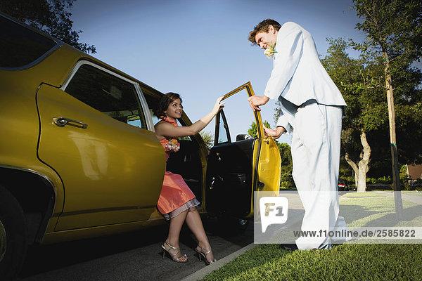 Junge Frau wird von Prom Datum Auto geholfen