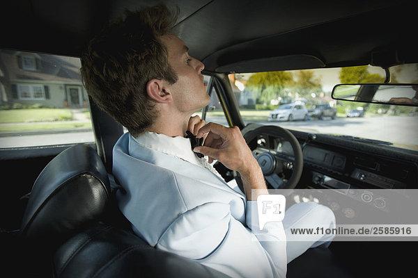 Junger Mann Kontrolle Fliege in Auto-Spiegel